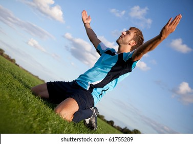 Football player celebrating with arms open outdoors