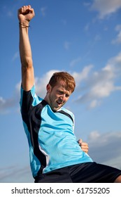 Football player celebrating with arms up outdoors