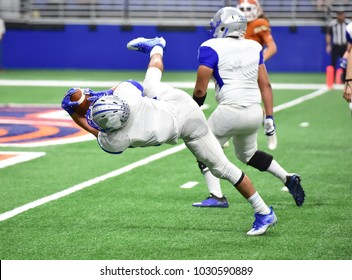 Football player diving forward for a touchdown during a game