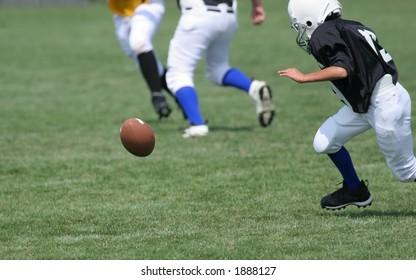 A football player fumbles ball.