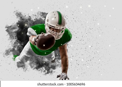 Football Player with a green uniform coming out of a blast of smoke.