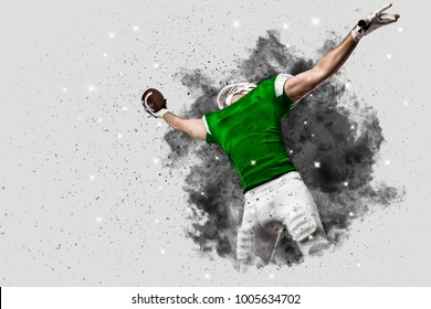 Football Player with a green uniform coming out of a blast of smoke, catching a ball.
