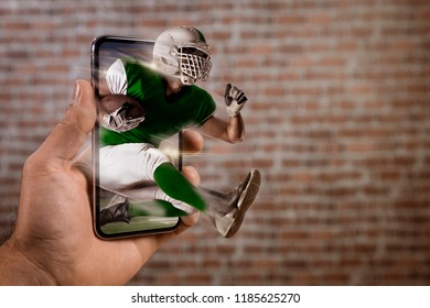Football Player with a green uniform playing and coming out of a full screen phone in front of a brick wall. Watching a football game on demand concept. copy space.