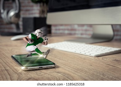 Football Player with a green uniform playing and coming out of a full screen phone on a wooden table. Watching a football game on demand concept. copy space.