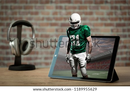 Football Player with a Green uniform playing and coming out of a tablet. Watching a football game on demand concept.