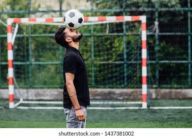 Football player hitting a ball with his head on field, time for play..