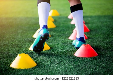 Football player Jogging and jump between cone markers on green artificial turf for football training. Football or Soccer Academy.