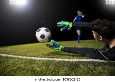 Football player kick ball and goalkeeper try to catch the ball and save goal