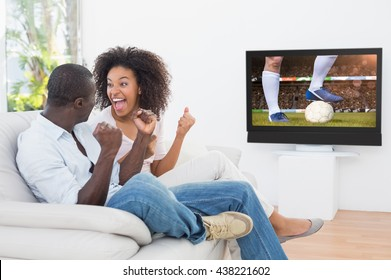 Football player kicking ball against couple sitting on couch together watching tv