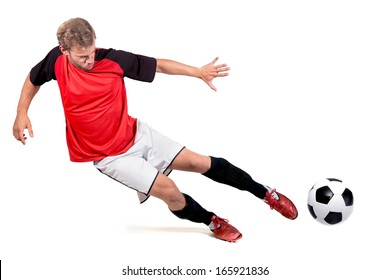 Football player kicking a ball isolated in white