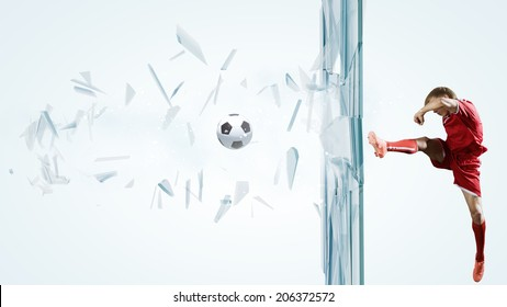 Football player kicking ball in jump and breaking glass