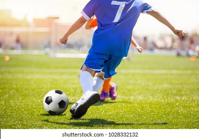 Football Player Kicking Ball on Grass Pitch. Soccer Striker Scoring Goal