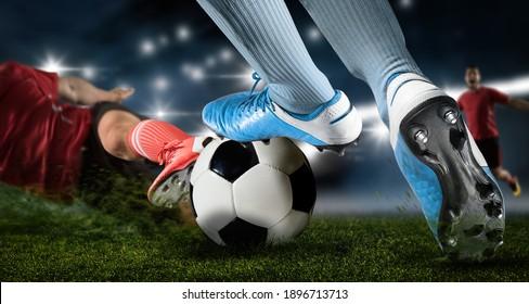 暗いアリーナ背景にフットボールの選手の男性が活躍している。 サッカー選手が滑り止めを作る