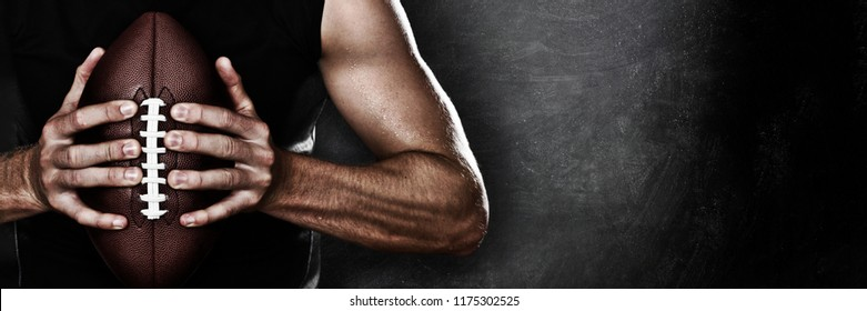 Football player man player holding american football on black blackboard texture background with copy space for text or design. Panoramic banner.