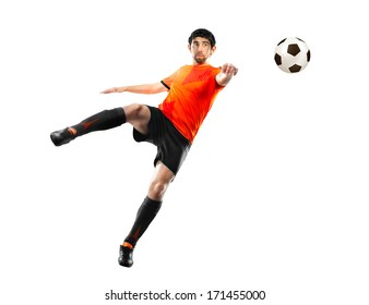 football player in orange shirt striking the ball at the white background