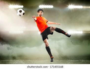 football player in orange shirt striking the ball at the stadium
