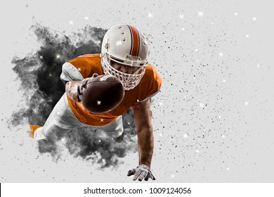 Football Player with a orange uniform coming out of a blast of smoke.