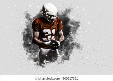 Football Player with a Orange uniform coming out of a blast of smoke .