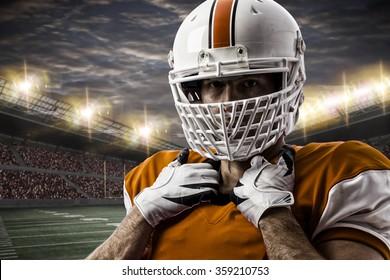 Football Player with a orange uniform on a stadium.