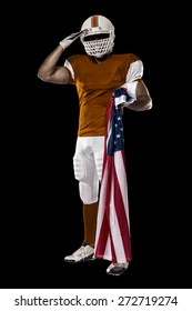 Football Player with a orange uniform saluting with a american flag, on a black background.