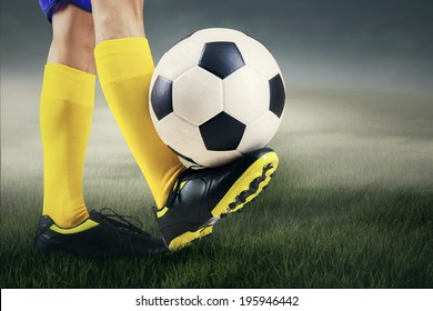 Football player is playing soccer ball at field