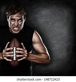 Football player portrait holding american football staring aggressive looking at camera on black chalkboard background with copy space for text or design. Caucasian male model in his 20s.