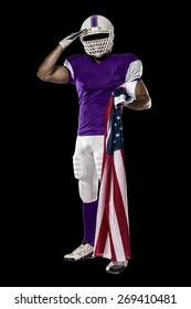 Football Player with a purple uniform saluting with a american flag, on a black background.