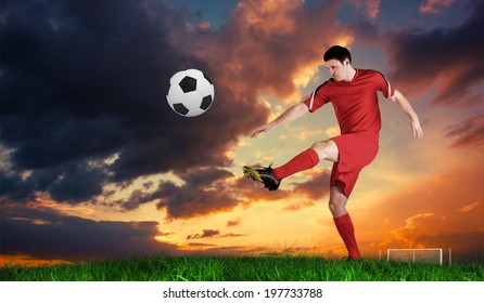 Football player in red kicking against green grass under blue sky