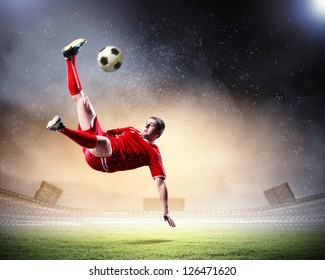 football player in red shirt striking the ball at the stadium under rain