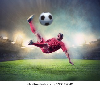 football player in red shirt striking the ball at the stadium