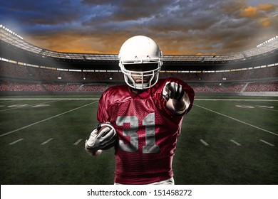 Football Player with a Red uniform celebrating with the fans.