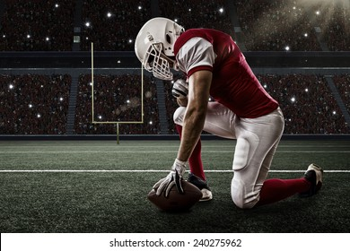 Football Player with a red uniform on his knees, on a Stadium.