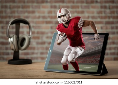 Football Player with a red uniform Playing playing and coming out of a tablet. Watching a football game on demand concept.
