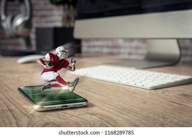 Football Player with a red uniform playing and coming out of a full screen phone on a wooden table. Watching a football game on demand concept. copy space.