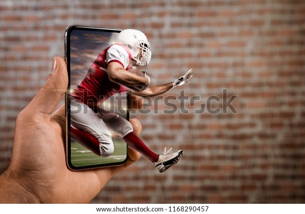 Football Player with a red uniform playing and coming out of a full screen phone in front of a brick wall. Watching a football game on demand concept. copy space.