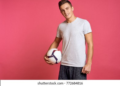 football player smiling in the hand ball on a pink background, sport