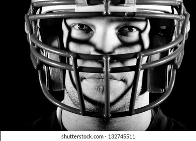 Football Player - This is a high contrast, black and white image of a young adult wearing a football helmet with an intense look on his face.