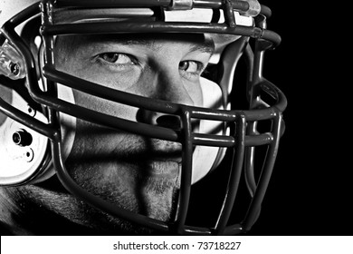 Football Player - This is a high contrast, black and white image of a young man with an intense look on his face wearing a football helmet. Processed to enhance skin texture.