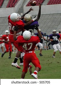 Football player trying to make a catch with defenders hanging on him