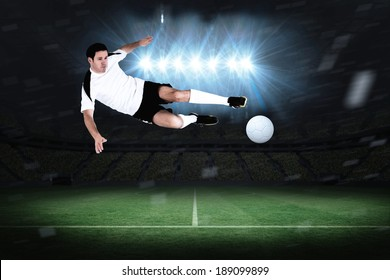 Football player in white kicking in a football pitch under spotlights