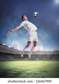 football player in white shirt striking the ball at the stadium