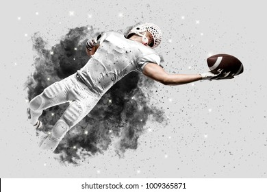 Football Player with a white uniform coming out of a blast of smoke, catching a ball.