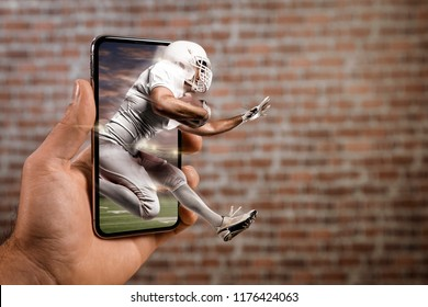 Football Player with a white uniform playing and coming out of a full screen phone in front of a brick wall. Watching a football game on demand concept. copy space.