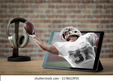 Football Player with a white uniform playing and coming out of a tablet. Watching a football game on demand concept.