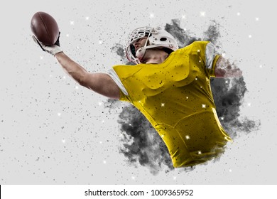 Football Player with a yellow uniform coming out of a blast of smoke, catching a ball.