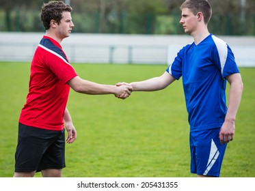 Football players in blue and red shaking hands on a clear day