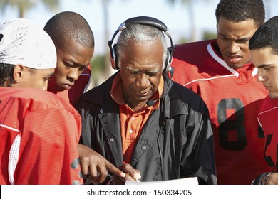 Football players and coach discussing strategy together