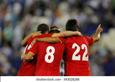Football players hugging while celebrate goal in a match