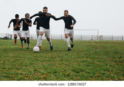 Football players practicing on field in the morning. Footballer kicking and running with the ball while other players run behind to take possession.