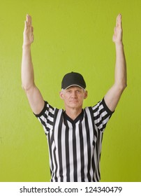 Football referee against green background signaling a touchdown, three quarter length,